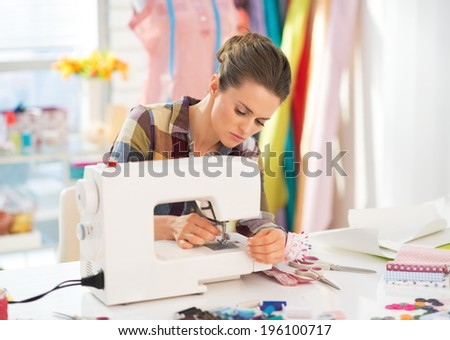 Seamstress working with sewing machine - stock photo