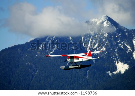 Seaplane flying over high mountain - stock photo