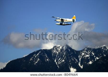 Seaplane flying over high mountain, Alaska - stock photo