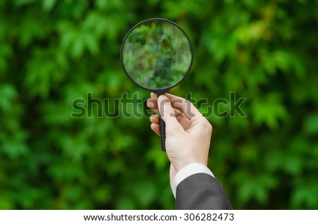 Search and business topic: hand in a black suit holding a magnifying glass on a background of green grass - stock photo