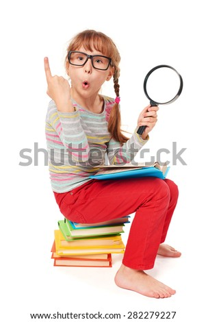 Search concept. Surprised little girl sitting on the pile of multicolor books, holding magnifying glass, over white background - stock photo