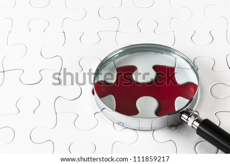 Search for missing puzzle pieces with a magnifying glass - stock photo