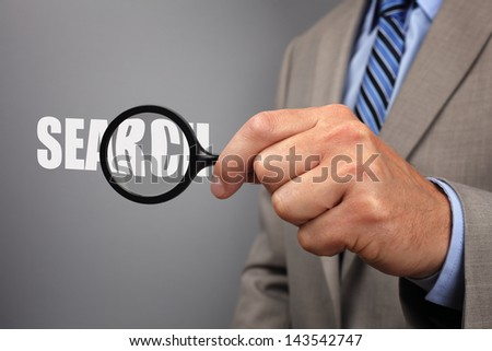 Searching businessman holding a magnifying glass across the word search - stock photo