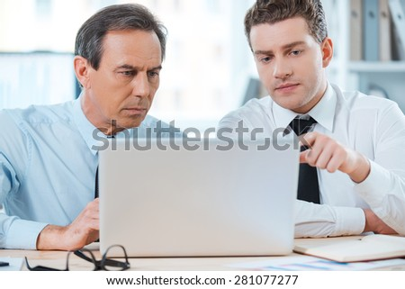 Searching for smart solutions together. Two serious business people in formalwear discussing something and looking at laptop while sitting at working place  - stock photo