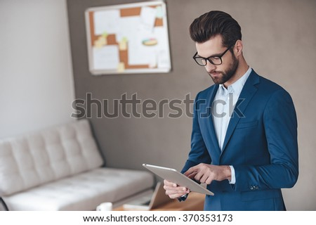 Searching for solution. Handsome young man wearing glasses and working with touchpad while standing in office - stock photo