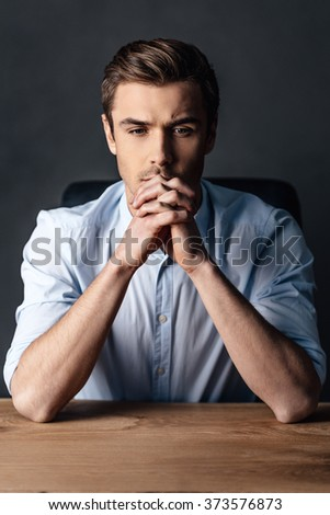 Searching for the right solution. Handsome young man keeping hands clasped and looking thoughtful while sitting against black background - stock photo
