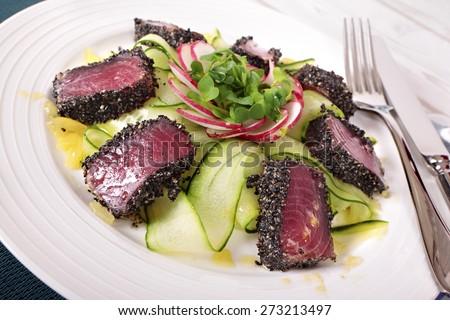 Seared ahi tuna with green salad on white plate. - stock photo