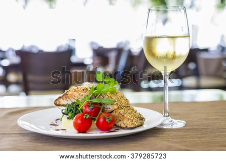 Seared salmon fillet with wine on restaurant background - stock photo