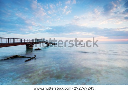 seascape and old bridge stretching into space, traveling to the seaside gives strength and energy. - stock photo