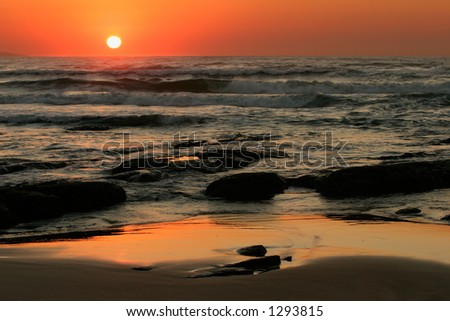 Seascape at sunrise with rocks in foreground - stock photo