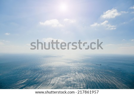 Seascape. Cargo ship in the sea on the background of the sky with white clouds. Storm at sea with divorces from the wind and the shadows of the clouds. Photographed in the summer on a hot sunny day. - stock photo