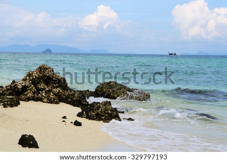 Seascape, coquina covered stones on seashore,     longtail boat and outlines of islands on horizon,scenic blue cloudy sky, Andaman sea, Koh Tup beach, Thailand, local soft focus, shallow DOF. - stock photo