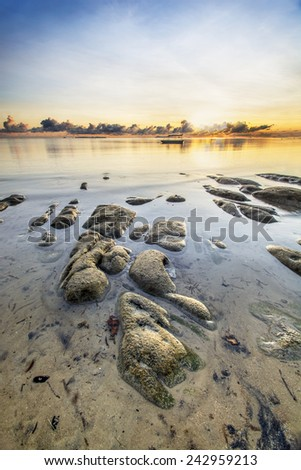 Seascape during sunrise with stones at the beach  (soft focus, Shallow DOF, slight motion blur ) - stock photo
