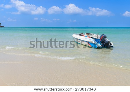 Seascape in the summer with a boat against sand beach and blue sky. - stock photo