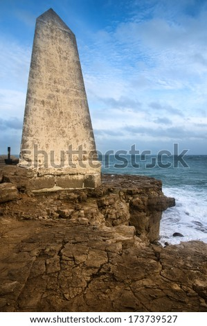 Seascape landscape of waves crashing onto rocks during beautiful Winter's day around memorial - stock photo