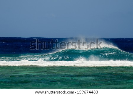 Seascape of a big wave break into a reef of a lagoon in Rarotonga, Cook Islands. - stock photo