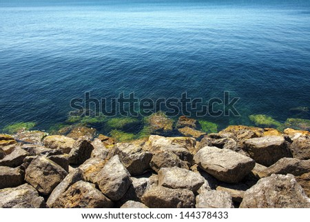 Seascape of calm blue ocean and rocky shore in the foreground - stock photo