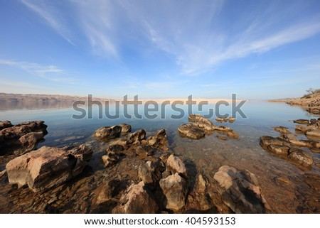 Seascape of croatian wild coast with stones in foreground and island in the background - stock photo