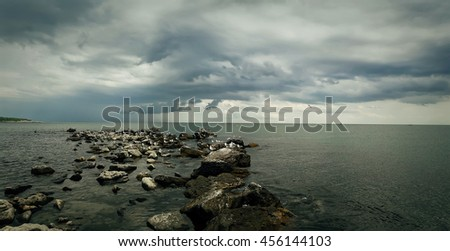 Seascape of stone beach with a dramatic cloudy sky. Beautiful view at the coast of the Black Sea in Balchik city, Bulgaria. - stock photo