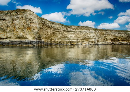 seascape, rocks against a blue sky with clouds reflected in the water - stock photo