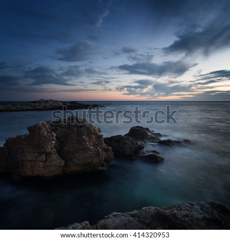 Seascape. Sea coast under blue sky with clouds at sunset - stock photo