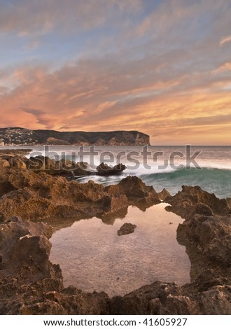 Seascape showing the sunrise on the Mediterranean coast, with a small pool of water on the rocky shore and a mountain in the background.  Warm colours of sunrise in the sky. - stock photo