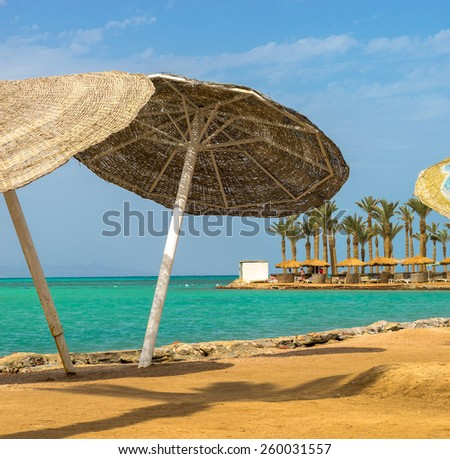 Seascape with beach umbrellas on a tropical beach. Resort vacation on a island of summertime.  - stock photo