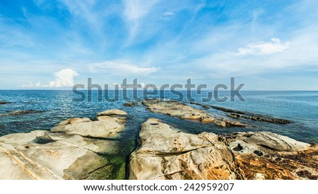 Seascape with stones at the beach and blue sky (soft focus, Shallow DOF, slight motion blur ) - stock photo