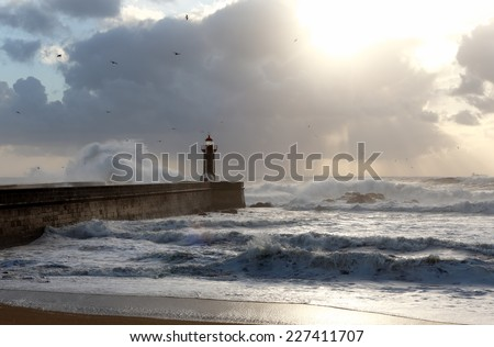 Seascape with strong waves crashing against the lighthouse and pier and interesting end-of-day light filtered through the clouds and moisture. Porto, Portugal, in January. - stock photo