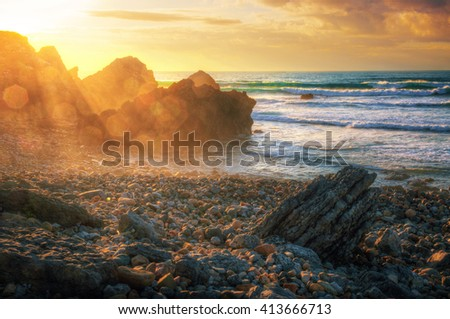 Seascape with sun beams at sunset in Abano Beach, Portugal. - stock photo