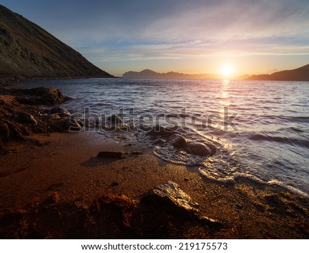 Seascape with sunset. The mountains and hills at the seaside are painted in orange color on the background sky with clouds. Small waves on the water and reflections. - stock photo