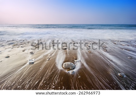 seascape with wave foam over the rocks - stock photo