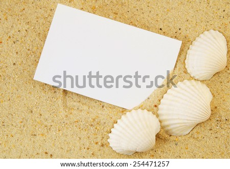 Seashell and blank card on sand - stock photo