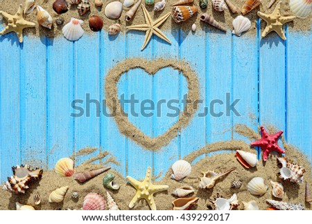 Seashells and starfish on a blue wooden background. Silhouette of the heart made of sand - stock photo