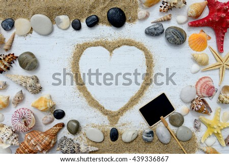Seashells and starfish on a white wooden background. Silhouette of the heart made of sand - stock photo