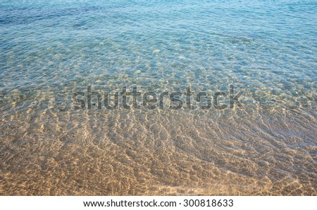 Seashore background with clear blue sea water, waves and golden sandy beach - stock photo