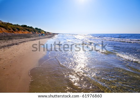 seashore with waves and foam and blue sky - stock photo