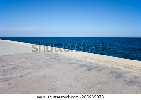 Seaside background, wide concrete pier by the sea. - stock photo