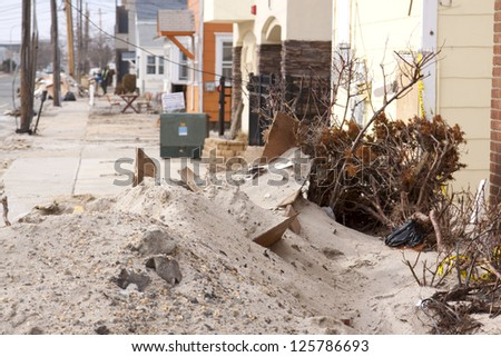 SEASIDE HEIGHTS, NJ - JAN 13: Sand and debris block a sidewalk on January 13, 2013 in Seaside Heights, New Jersey. Clean up continues 75 days after Hurricane Sandy struck the shore in October 2012. - stock photo