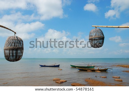 Seaside landscape with fishing boats and traditional crab baskets - stock photo