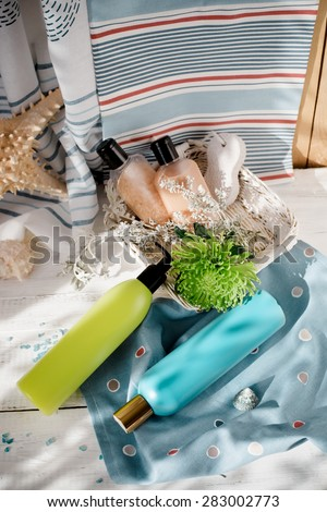 Seaside spa: shower gels, body creams, foot pumice and a flower, set with seashells and home decorations, marine theme, natural light shot. Toned photo. - stock photo