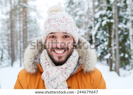 season, christmas and people concept - happy smiling young man in snowy winter forest - stock photo
