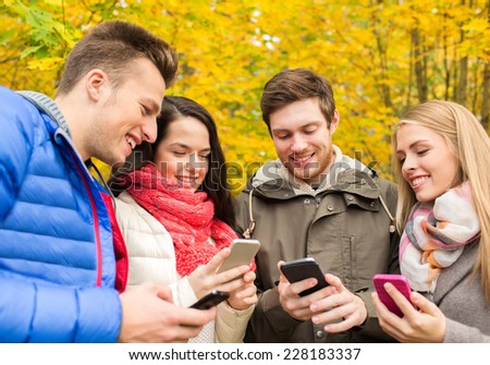 season, people, technology and friendship concept - group of smiling friends with smartphones in autumn park - stock photo
