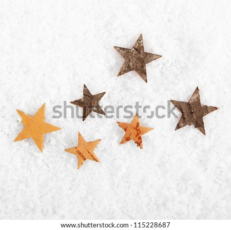 Seasonal or Christmas background of scattered rustic stars on fresh white winter snow with copyspace - stock photo