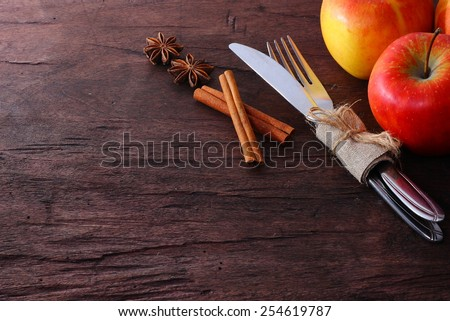 Seasonal table with cutlery and apple - stock photo