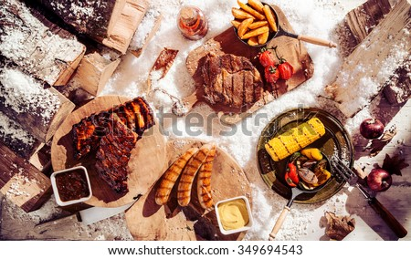 Seasonal winter barbecue in snow with grilled spicy steak, ribs and sausages served with assorted grilled vegetables and potato wedges, overhead view - stock photo