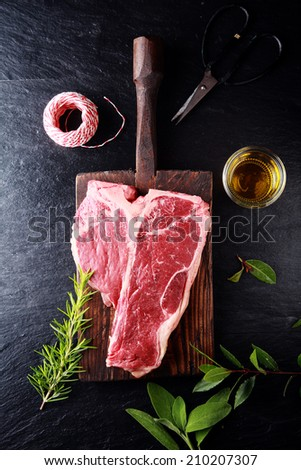Seasoning a t-bone steak for cooking with bay leaves, fresh rosemary, olive oil and string, overhead view on a wooden board on a rustic kitchen counter - stock photo