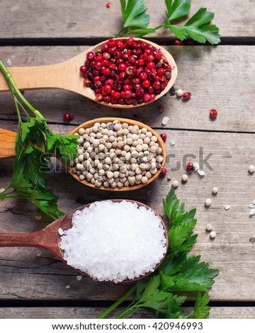 Seasoning for cooking.  Red and white pepper and sea salt in wooden spoon on aged wooden background. Food ingredient. Selective focus. Flat lay. - stock photo