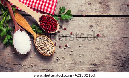 Seasoning for cooking. Red and white pepper and sea salt in wooden spoon on aged wooden background. Food ingredient. Selective focus. Place for text. Flat lay. Top view. Toned image. - stock photo