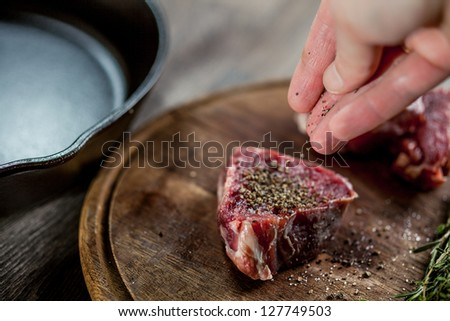 Seasoning tenderloin steaks with ground pepper - stock photo